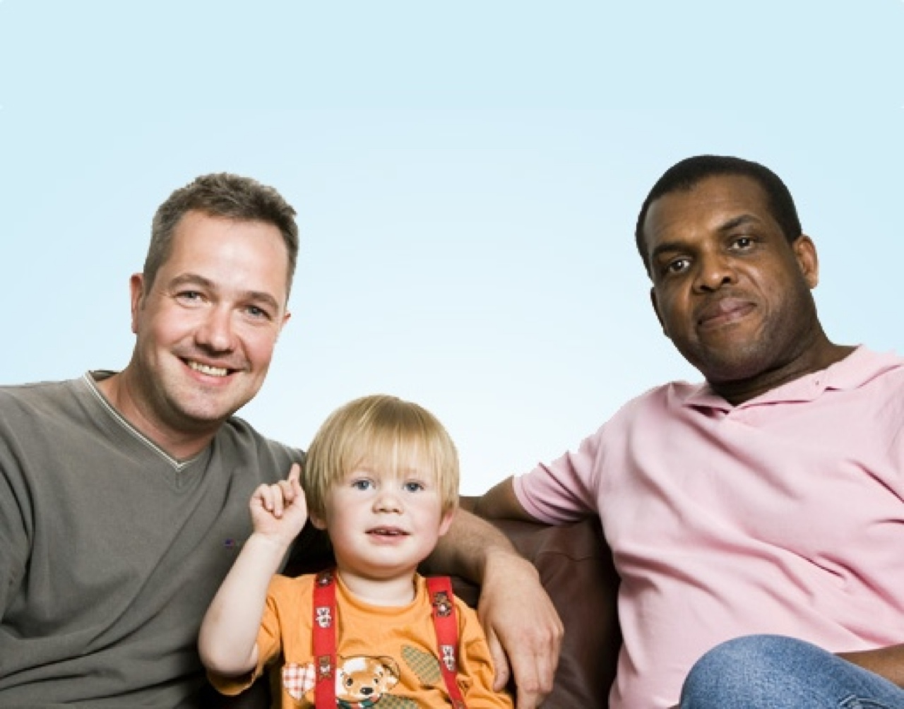 Two middle aged men with a small child